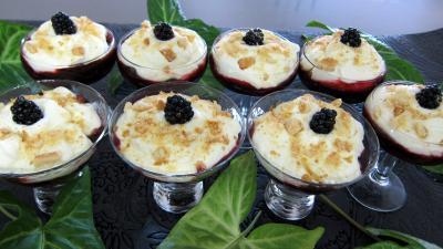 Couvrir la préparation aux mûres de la crème et décorer d'une mûre et du reste de biscuits hachés